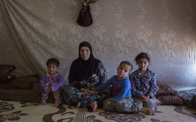Ayda sits with her grandchildren in her home