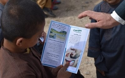 Children read some material provide by Concern at a Global Handwashing Day Ceremony. The event covered important topics including safe drinking water, open defecation, and personal hygiene. Photo: Concern Worldwide
