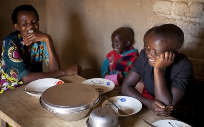 Violette Bukeyeneza sitting at her new kitchen table with her children, Amida Tuyishimire, Rashid Niyogushimwa, Lievain Irankunda, Idrissa Nzoyisaba 8, and Ghyslaine Iteriteka 6. Photo: Abbie Trayler-Smith / Concern Worldwide.
