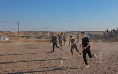 In northwest Iraq, Michael Darragh MacAuley joins in on a game of soccer on some open ground. Photo: Gavin Douglas/Concern Worldwide.