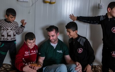 Michael Darragh Macauley meets with children living at an Iraq refugee camp.