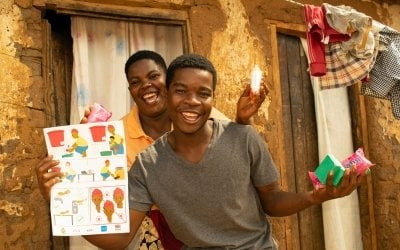 Patricia Moloko with her son George pictured with the soap and Covid-19 fliers they have received from Concern Malawi.