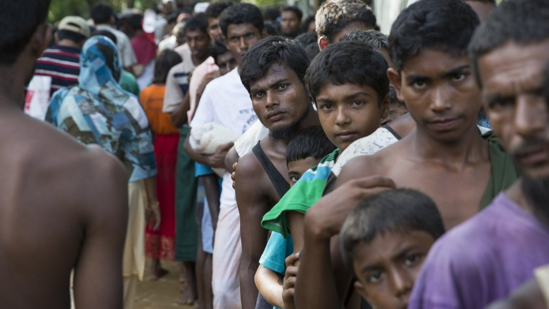 Rohingya men from Myanmar queue at a distribution site at Hakim Para in Cox's Bazar, Bangladesdh. Photo: Kieran McConville / Concern Worldwide.
