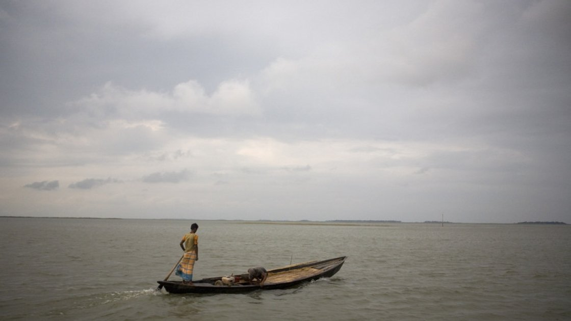 A lone boatman travels accross the Haor flood plains of North East Bangladesh.