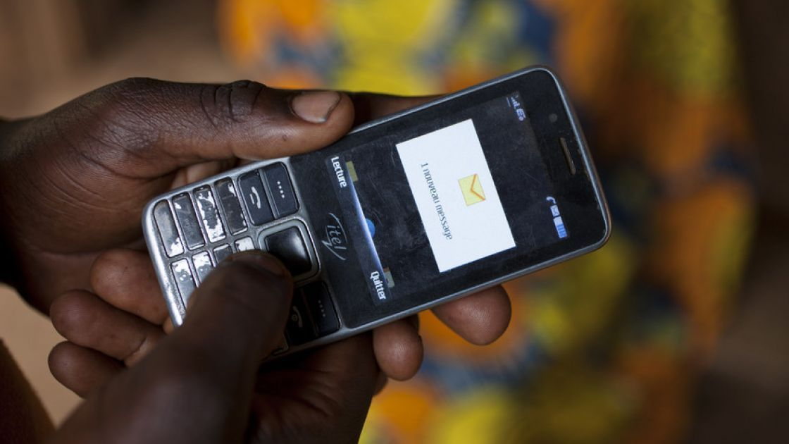 Olivier Irankunda (23) uses his mobile phone at his home in Mabayi, Cibitoke.