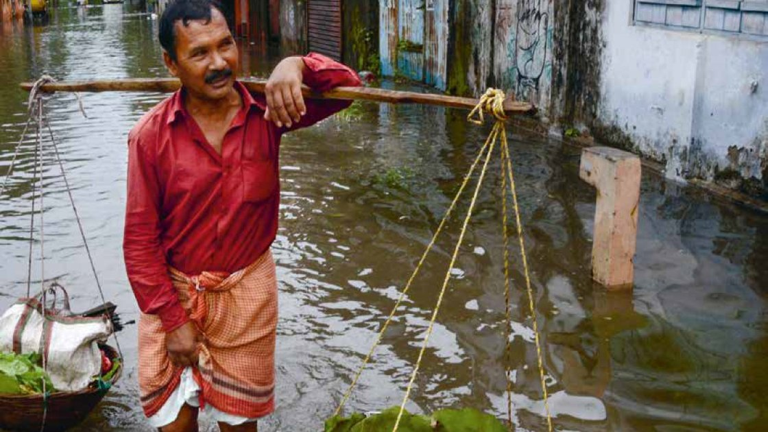 An Indian vegetable vendor carries his wares through floodwaters in Siliguri, West Bengal, on July 24, 2016. AFP/Diptendu Dutta 2016.