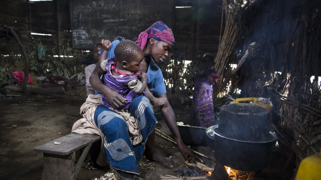 A woman sits with her child in her temporary accommodation.