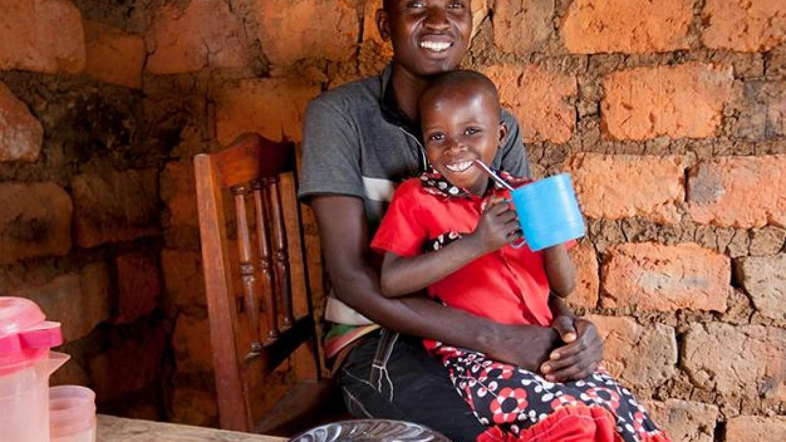 Megisela Muhoza (6) daughter of Gerard Ndabahekeye (28) at their new kitchen table and chairs. Photo: Abbie-Trayler Smith / Concern Worldwide.