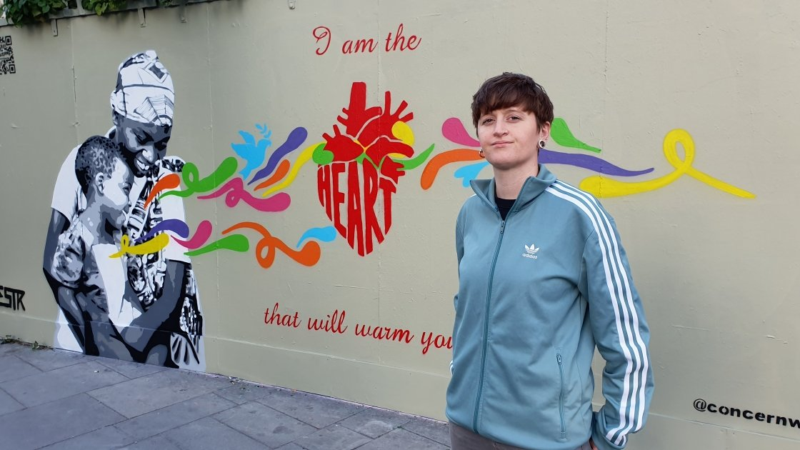 Artist Emmalene Blake standing in front of the mural she painted for International Day of Peace. Photo: Concern worldwide.