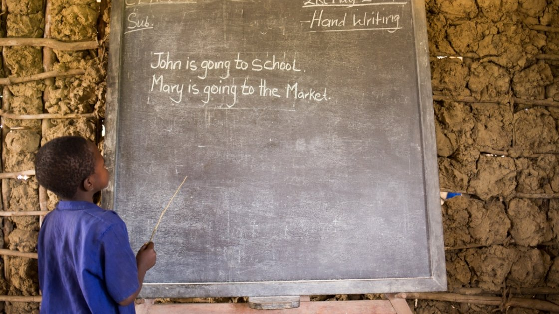 An SLMB Masaba Primary School pupil engages in Literacy, Kunike Barina in Tonkolili, Sierra Leone, 2014. Photo: Michael Duff / Concern Worldwide.