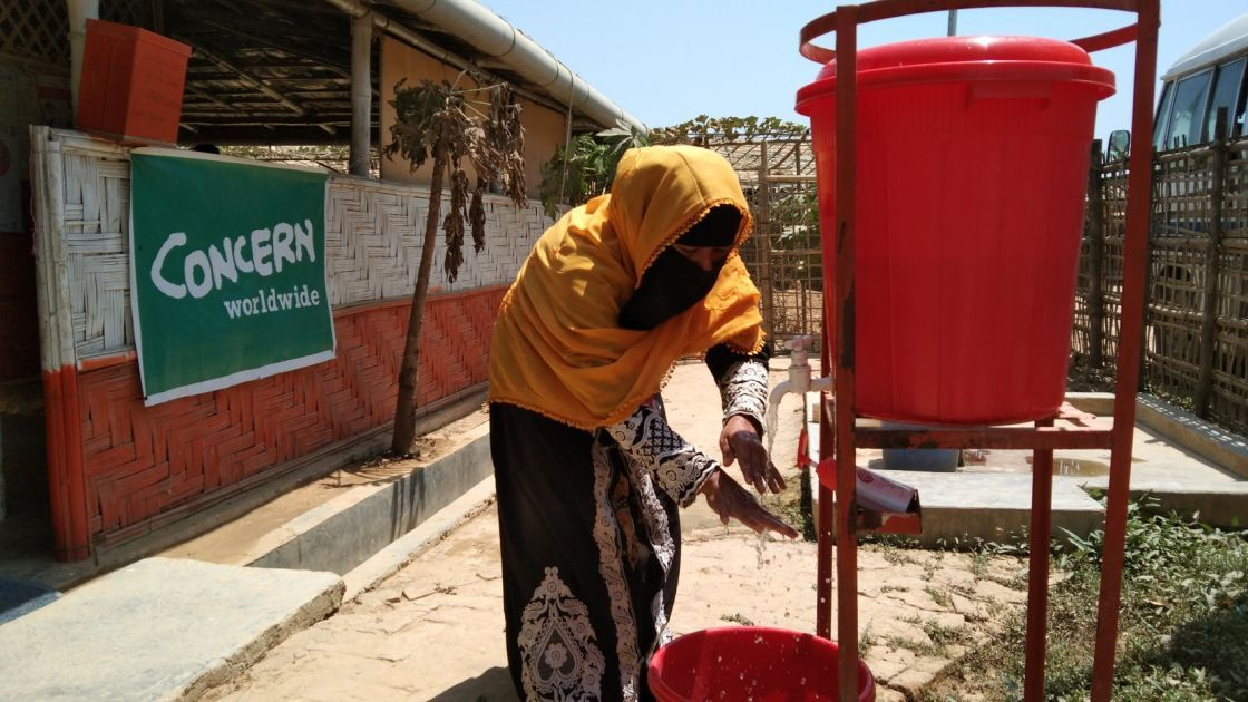 A woman washes her hands, with a Concern banner in the background