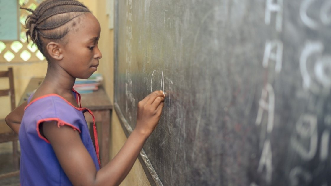 A student in class 1 at Benevolent Islamic Primary School in Makinth community in Sierra Leone writes on the black board, 2015. Photo: Michael Duff / Concern Worldwide.