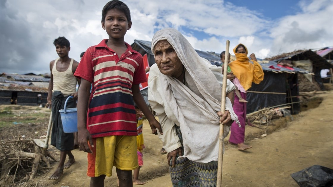 Moburak*, aged eight, leads his grandmother Nur* through Moynadhona refugee camp for Rohingya in Cox's Bazar, Bangladesh. Photo: Kieran McConville/Concern Worldwide.