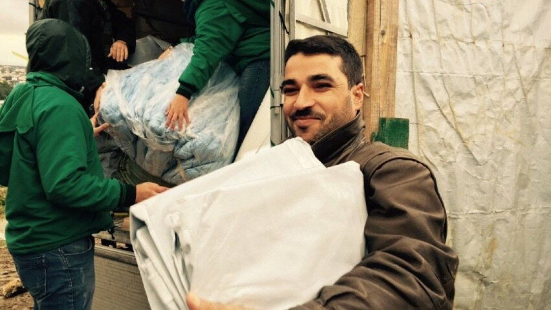 Ahmad el Ezzou receiving Non Food Items at an informal settlement in Lebanon. Photograph taken by: Amanda Ruckel/Concern Worldwide.
