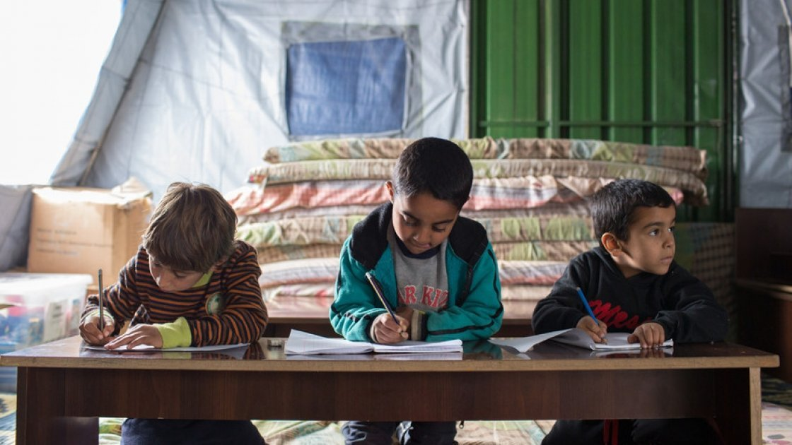 Syrian refugee children write on their notebooks during class at an informal tented settlement in Akkar, Lebanon. Photo taken by Dalia Khamissy / Concern Worldwide.