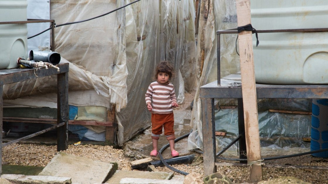 A Syrian refugee child stands next to the water tanks at an informal tented settlement in in Akkar, northern Lebanon. Photo taken by Dalia Khamissy / Concern Worldwide.