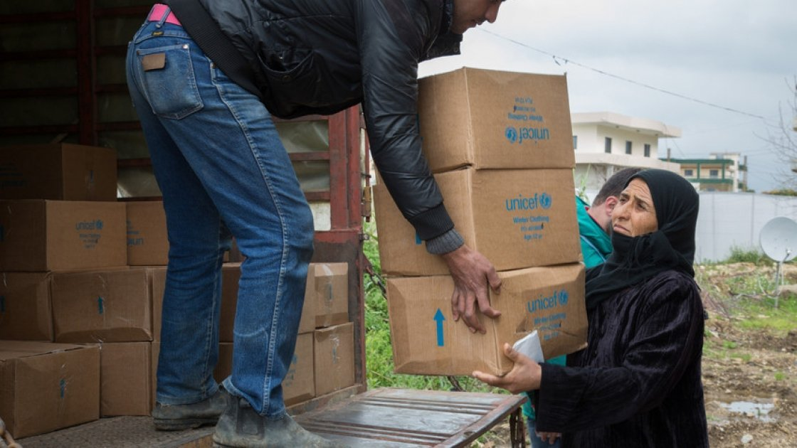 A Syrian refugee woman receives winter clothes distributed to Syrian refugees by the Concern Worldwide team at the informal tented settlement in Akkar, northern Lebanon.Photo taken by Dalia Khamissy/ Concern Worldwide.