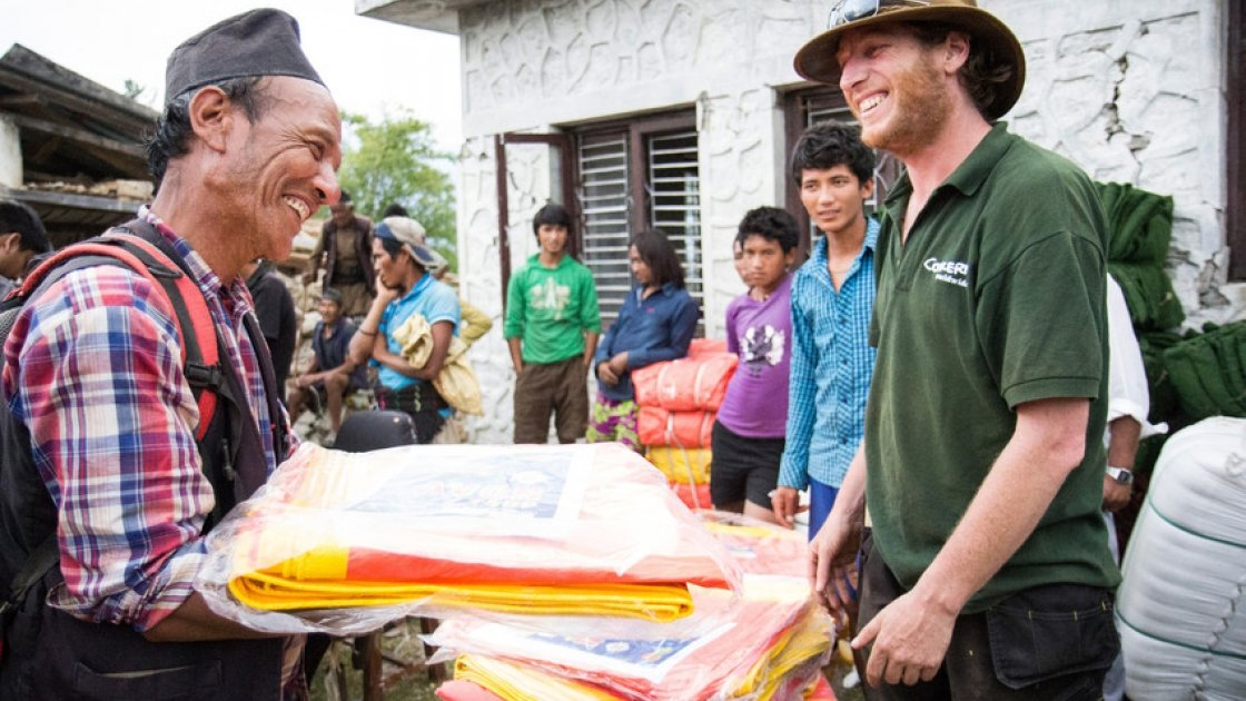 Concern Worldwide's Dom Hunt distributes tarps in Mane Banjang, a community high in the foothills in Sindhupalchok district, one of the hardest hit areas by the 7.8-magnitude earthquake that struck Nepal on 25 April. Photo taken by Crystal Wells / Concern Worldwide.
