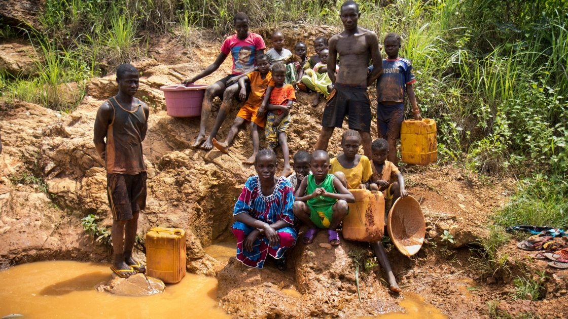 Residents of Gaga village gather beside a local spring, that is often used by locals to mine for gold, to collect water for drinking, cooking and other household needs. Photo: Crystal Wells/Concern Worldwide.