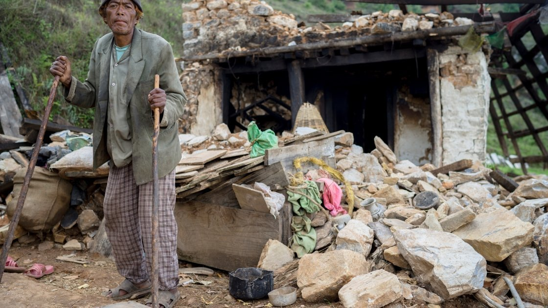 Pasairingi Sherpa, 60 years of age, stands outside his home in in Hawa VDC, Ward 6, Nepal that was destroyed in the earthquake. Photo taken in June 2015 by Brian Sokol/Concern Worldwide.