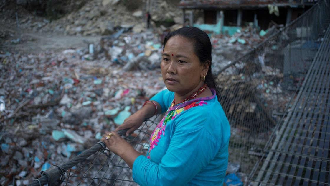 Sua Tamang overlooks the devastation caused by the earthquake in Dolakha District. Credit: Brian Sokol/Concern Worldwide.