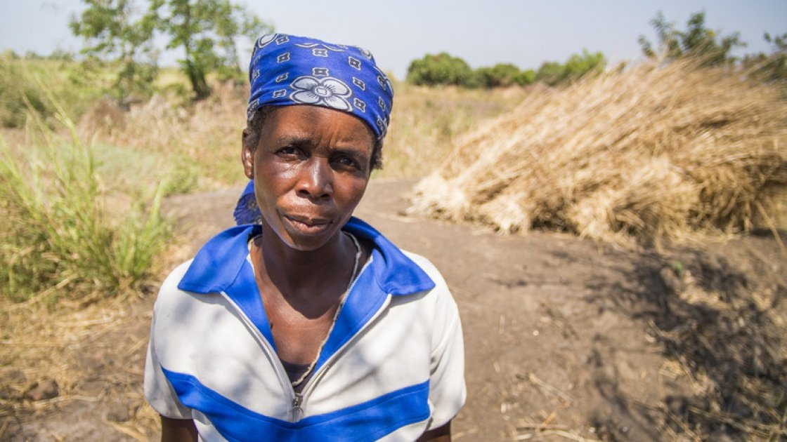 Lucia White in front of the site of the home she lived in for 20 years in Nsanje, Malawi. The house was washed away by the floods of January 2015. Lucia has been helped by Concern with emergency supplies and with seeds, fertilizer and goats. Photograph taken by: Concern Worldwide/Kieran McConville.