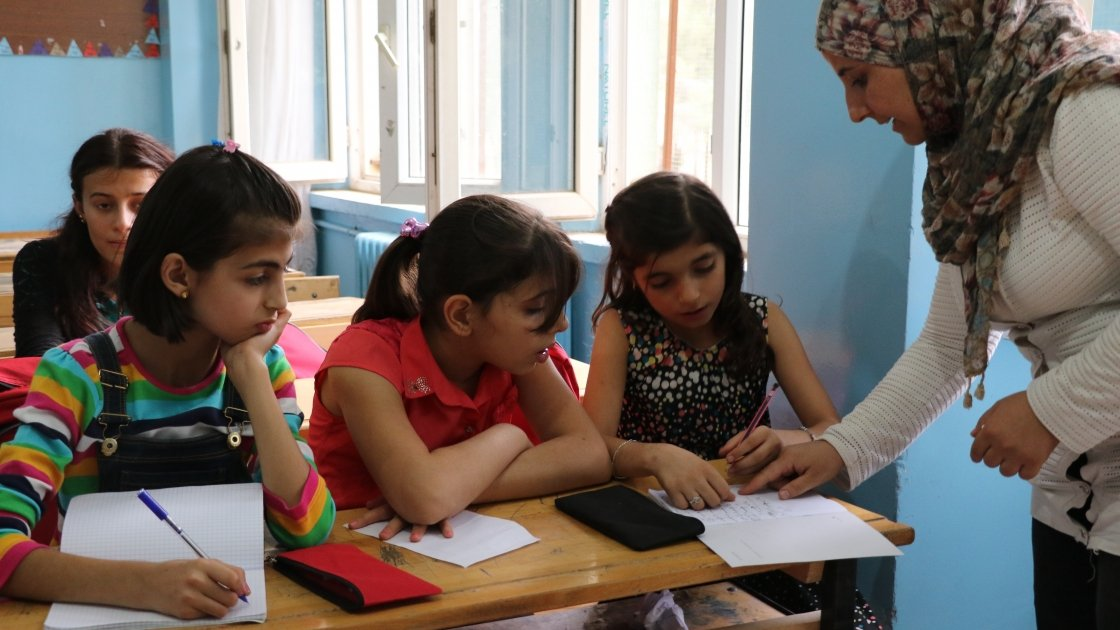 A teacher helps young students with their school work.