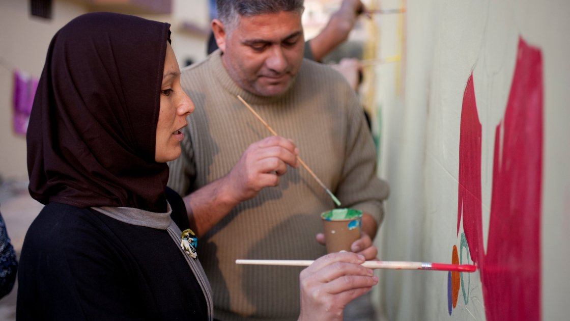 Tarek and Zeinah attend an art workshop with refugee families at a Concern supported Collective Centre in Northern Lebanon in December 2015. Zeinah and Tarek now live with their three children and two other families. Photo: Panos Pictures/Concern Worldwide.