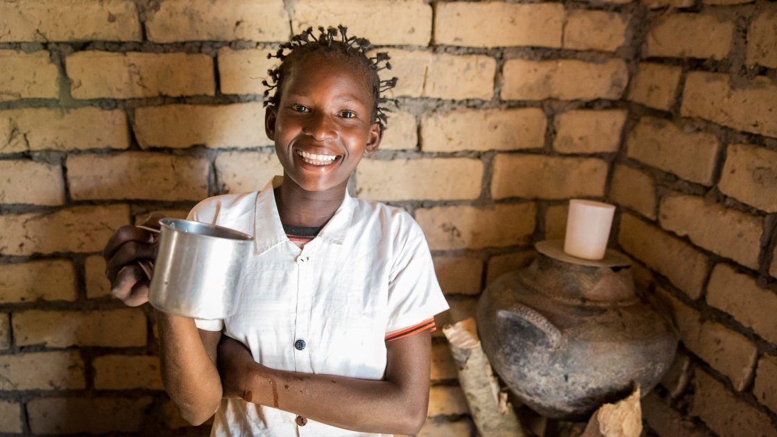 Liliana from Mulombwa in DRC proudly holds a cup of clean water. The DRC WASH Consortium worked with her community to raise awareness about water, sanitation and hygiene and build a water pump in the village. Photo: Kieran McConville/Concern Worldwide.