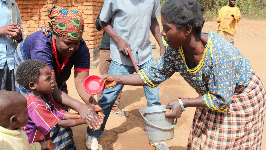 Members of the Mbachundu village Community-based Childcare Development Centre (CBCC) providing water for children to wash their hands before eating. Concern provided the centre with a water filter so these children have access to clean water for cleaning and drinking. Date: July, 2016. Photo: Aoife O'Grady/Concern Worldwide.