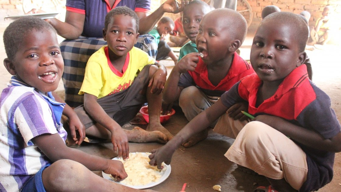Vent Chimangeni, Emmanuel David, McDonald Mathew and brothers Anderson and Geofrey Mbewe from Mbachundu village, Mchinji, Malawi eat a mix of corn, soy and ground nuts which the Concern team trained their community to prepare. Photo: Aoife O'Grady/Concern Worldwide.