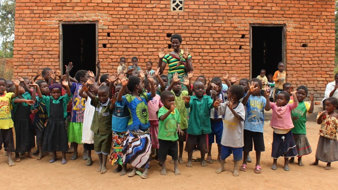 Caregiver Lustilla Mathew of the Mbachundu village Community-based Childcare Centre (CBCC) leads the children of the village in a game. Concern is supporting centres like this across the Mchinji district of Malawi. Photo: Aoife O'Grady/Concern Worldwide.