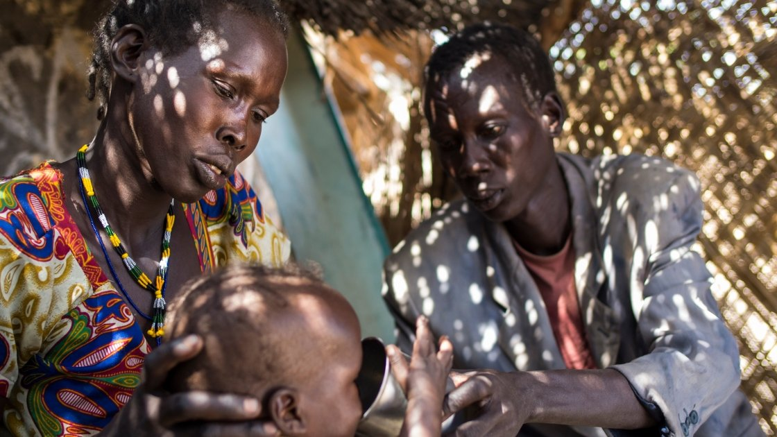 Atuil Chok with her husband, Adim, with their fourteen month old twins, who have both been acutely malnourished and are attending the outpatient therapeutic programme run by Concern in Maduany in Aweil North, South Sudan. Photo: Kieran McConville/Concern Worldwide.
