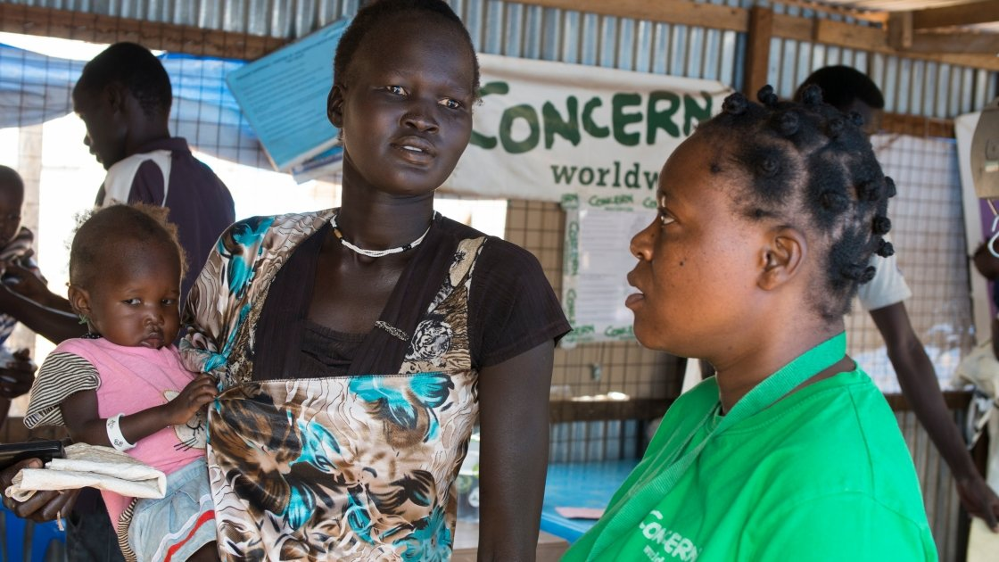 Nyakong Kwach and her 12 month old daughter, Nyadhabitat, talk with Concern nutritionist, Tracy Dube at the Concern nutrition centre in a refugee camp in Juba, South Sudan. They took shelter here after fighting broke out in July 2016. The centre is currently seeing between 60 and 70 new cases a week. Photo: Kieran McConville/Concern Worldwide.
