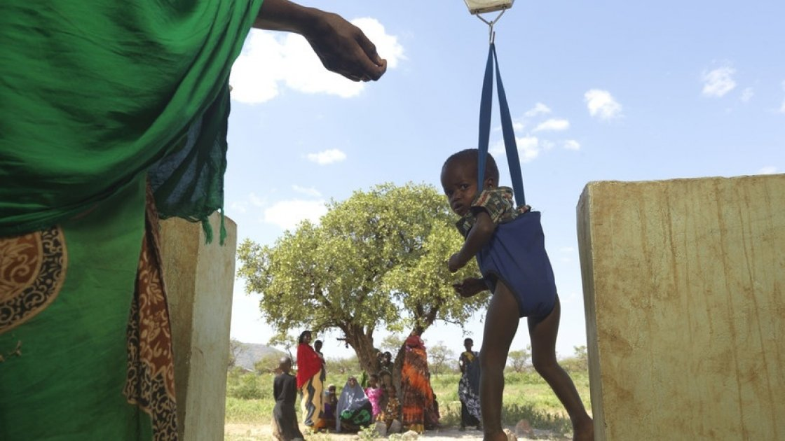 A malnourished child is weighed by Community Health Volunteers in Kenya. Photo: Peter Caton / Concern Worldwide