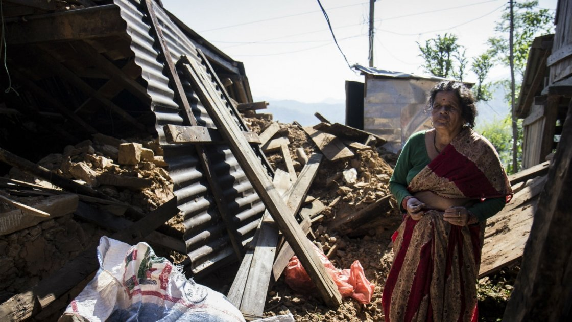 In a Nepalese village, Chandra stands amongst the wreckage of her home. Photo taken by Crystal Wells/Concern Worldwide