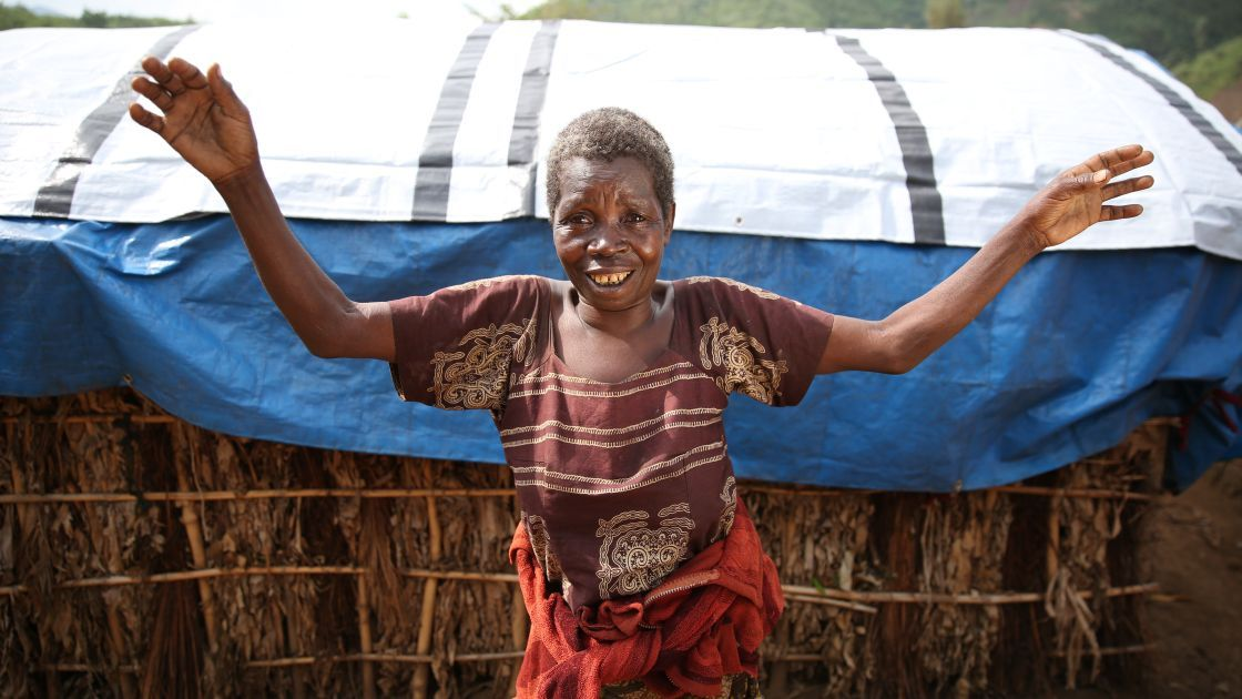 68 year old widow, Kataina Mutoo, shows off her new tarpaulin at Bushani camp in Masisi, DRC, which she received as part of a Concern Worldwide distribution, DRC, 2017. Photo: Jennifer Nolan / Concern Worldwide.