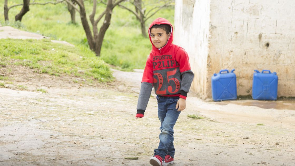 Kareem* walking to Concern's non-formal education learning centre near his home in northern Lebanon. Photo: Chantale Fahmi/Concern Worldwide 2017.