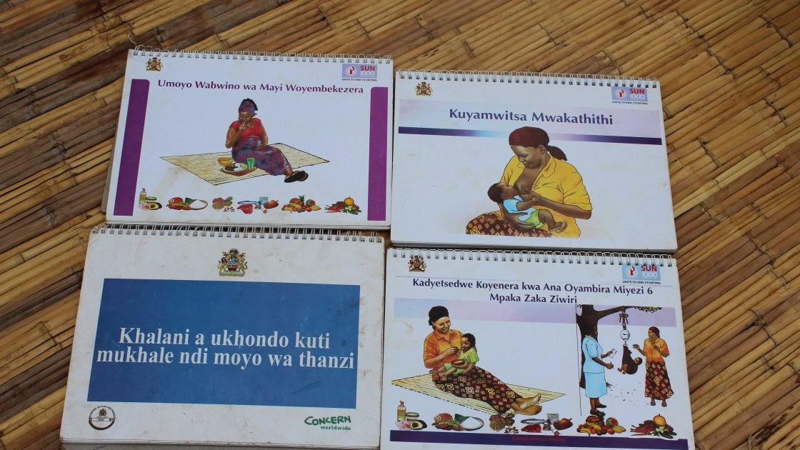 Publications used by a cluster of mothers in Louna village as part of the Support Nutrition Improvement Component (SNIC) project, implemented by Concern in the Mchinji district of Malawi. The publications are used to teach cluster members about the benefits of good nutrition and hygiene practices, exclusive breastfeeding and family planning to help improve the health of mothers and babies and prevent malnutrition. Photo: Aoife O'Grady/Concern Worldwide.