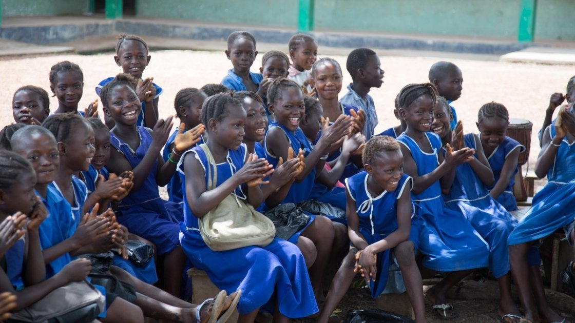 Students clap during a school clubs drama skit on gender at UMC Primary School, Masengbeh Community, Sierra Leone. Photo taken by Michael Duff.