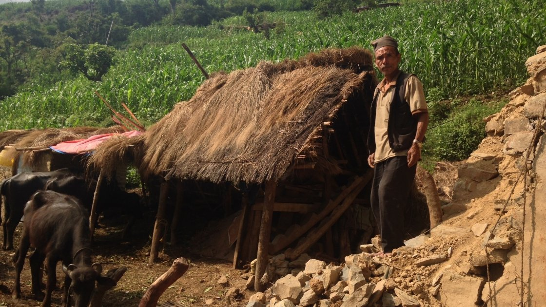 Dhan Bahadhur Waiva stands on the debris of his house in the remote, rural village of Rambheda, Sindhuli, Nepal. Photo taken by Daniel Gray/Concern Worldwide.