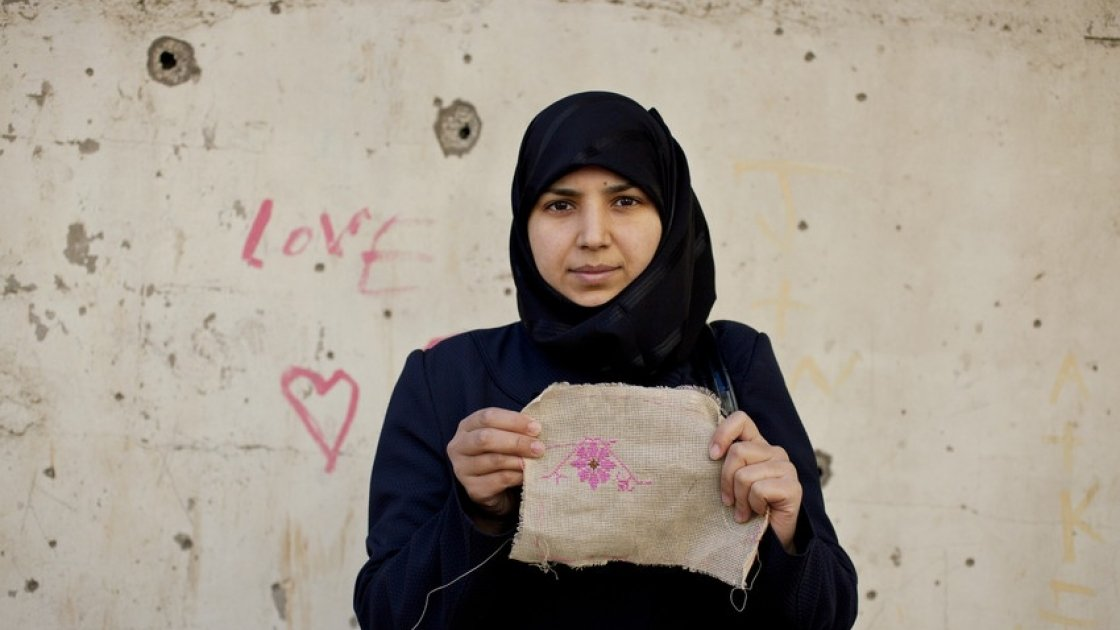 Layal, 27 a refugee from Syria, holding her embroidery as part of a programme to reduce tensions and earn some income through embroidery. Photo by Abbie Trayler-Smith/Panos, Lebanon 2016