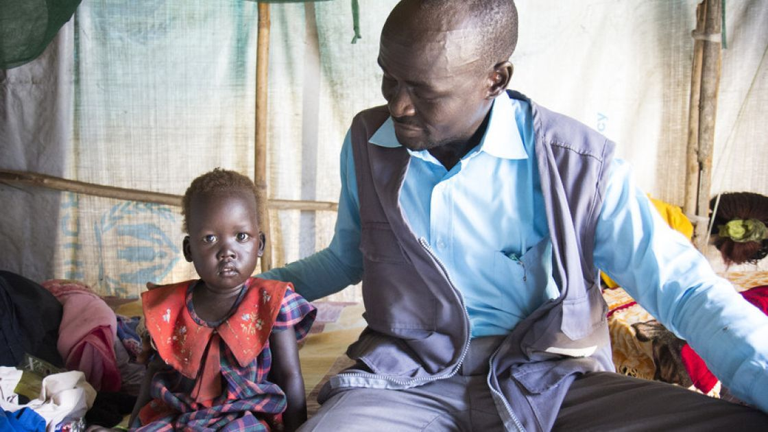 Nyakan, 3, sits in her home in Juba, South Sudan with Concern Worldwide nutrition programme staff member Lony Gatweech. Photo taken by Crystal Wells, Concern Worldwide.