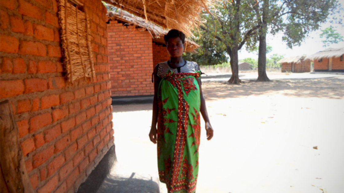 Christina stands outside her home in rural Malawi. Photo taken by Alice Gandiwa.