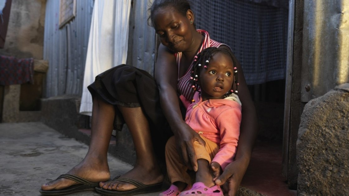 Scholastica Mbinya always makes sure  Francisca puts on her shoes before leaving the house. Photo: Peter Caton / Concern Worldwide