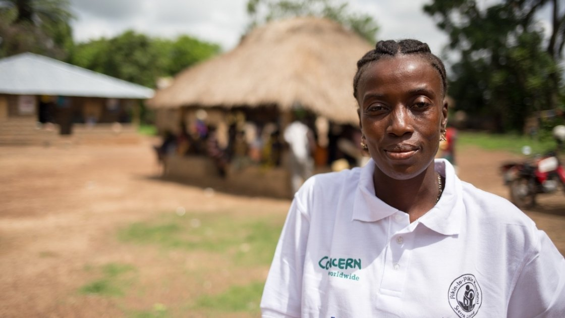 Ramatu S. Kamara pictured outside the community conversation club in Mamondor, in Tonkolili District, Sierra Leone. Photo taken by Michael Duff / Concern Worldwide 2014.