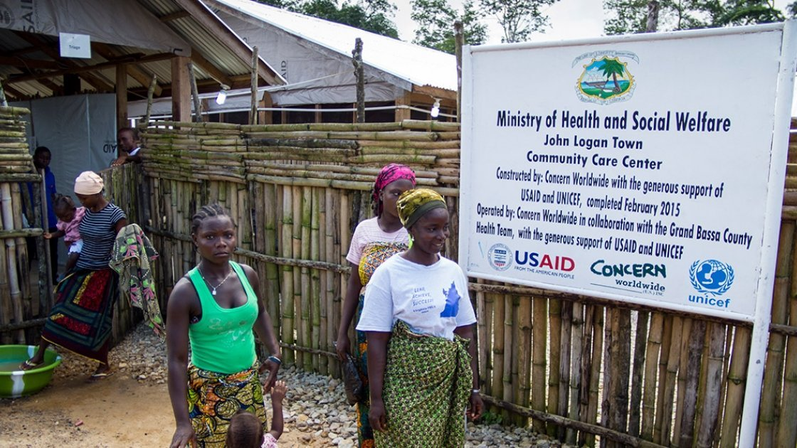 Women leaving the Community Care Center in John Logan Town, Grand Bassa County, Liberia. The center, built by Concern Worldwide, was designed to treat Ebola patients but has been transformed into a general health center. Photo taken by Kieran McConville/Concern Worldwide.