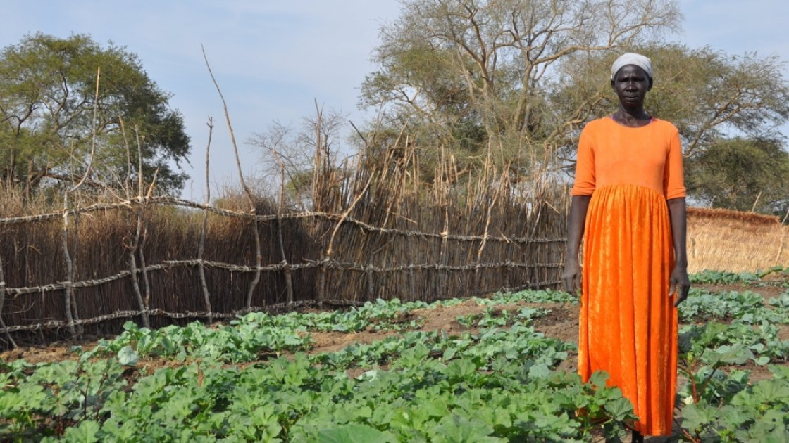 Namia stands proudly next to the vegetable garden she grew with the help of Concern. Photo taken by Deborah Underdown.