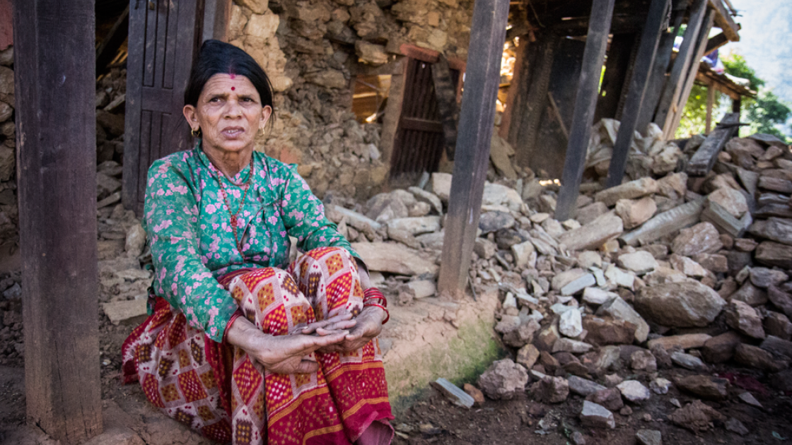 Tulasa Aryal sits on the porch of her earthquake-ravaged home in Bakrang, a village near the epicenter of the earthquake. Photo taken by Crystal Wells/Concern Worldwide.