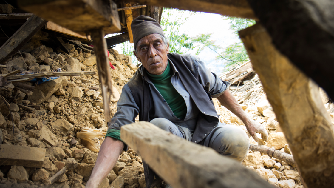 Seventy-year-old Krishna Prasad Sapkota digs through the mud and stones of what used to be his home to see if any belongings can be recovered. Photo taken by Crystal Wells/Concern Worldwide